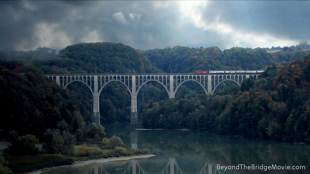 Still image from BEYOND THE BRIDGE: Wide shot of a viaduct-like bridge, which gets crossed by train. The bridge spans over a river and is surrounded by forrest, the sky is cloudy.